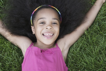 informant: Young girl lying on grass smiling