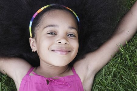 Close-up of a young girl lying on grass smiling LANG_EVOIMAGES