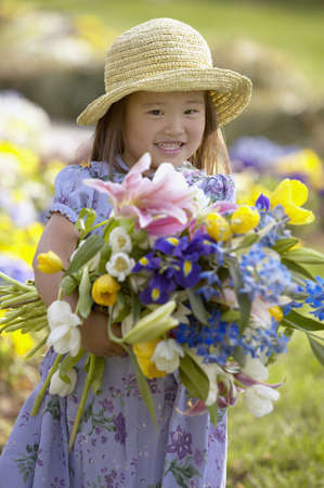 Young girl standing in a field holding flowers