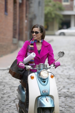 way of behaving: Mid adult woman riding a scooter