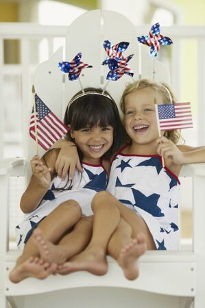 Two young girls sitting holding flags in their hands