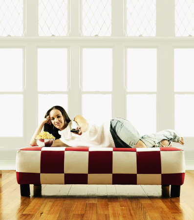 restfulness: Portrait of a young woman lying on couch