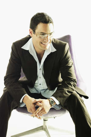 bifocals: Young businessman sitting on a chair smiling