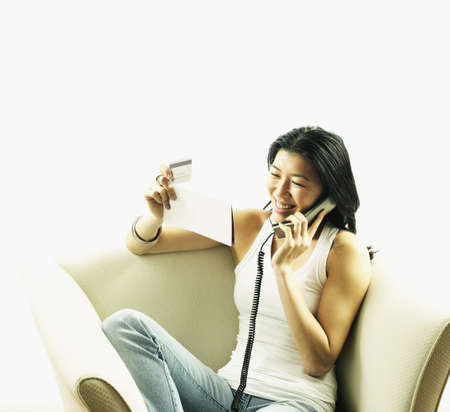 communicated: Young woman sitting on a couch holding a sheet of paper talking on a telephone