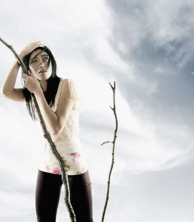 way of behaving: Young woman holding a branch of a tree