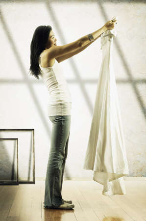 exploratory: Young woman standing holding up a dress