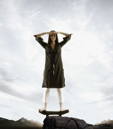 arousing: Portrait of a young woman standing on a platform on a rock