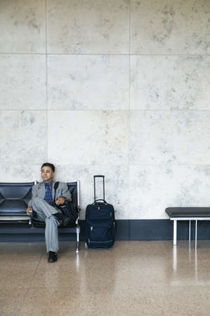1 person: Young businessman sitting in an airport with luggage