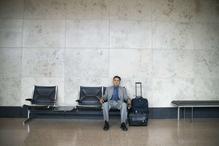 effrontery: Young businessman sitting in an airport with luggage
