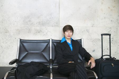 effrontery: Portrait of a young businesswoman sitting in an airport with luggage