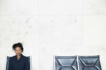 effrontery: Portrait of a young businesswoman sitting on a chair