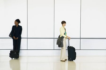 effrontery: Side profile of two young businesswomen standing in an airport with luggage