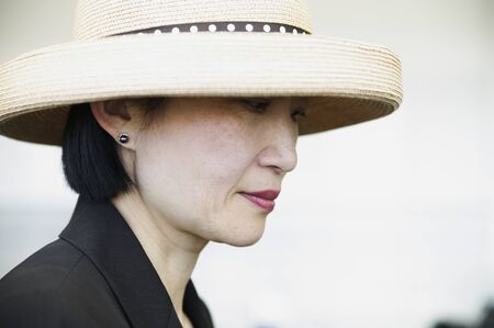 effrontery: Side profile of a businesswoman wearing a hat