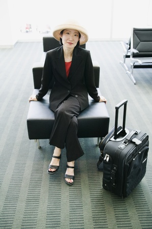 effrontery: Portrait of a businesswoman sitting in an airport lounge with luggage