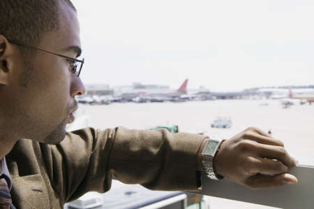 Side profile of a young businessman looking at his wristwatch Stock Photo - 16043748