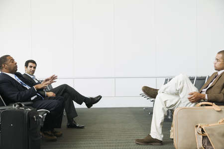 effrontery: Side profile of three businessmen sitting in an airport lounge with luggage