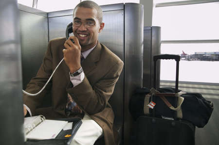credence: Young businessman using a phone booth in an airport