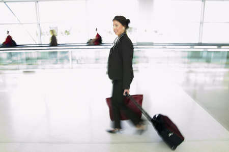 effrontery: Side profile of a businesswoman walking in an airport with luggage