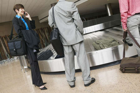 effrontery: Low angle view of business executives standing at a conveyor belt in an airport LANG_EVOIMAGES
