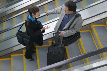 effrontery: High angle view of two business executives talking on an escalator