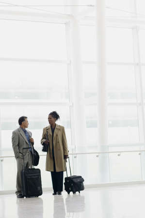 effrontery: Two business executives standing in an airport with luggage