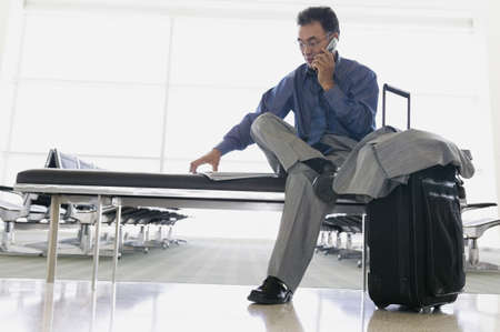 effrontery: Businessman talking on a mobile phone in an airport lounge LANG_EVOIMAGES