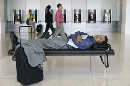 Side profile of a businessman sleeping on a bench in an airport lounge Stock Photo - 16043767