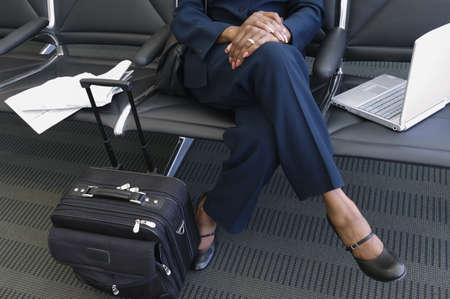 Close-up of luggage and a laptop lying beside a businesswoman in an airport lounge