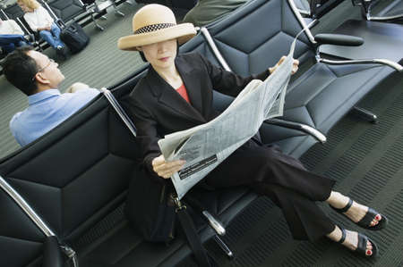 effrontery: High angle view of a businesswoman reading a newspaper in an airport lounge LANG_EVOIMAGES