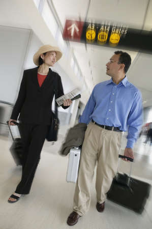 Two business executives walking in an airport with luggage Stock Photo - 16043771