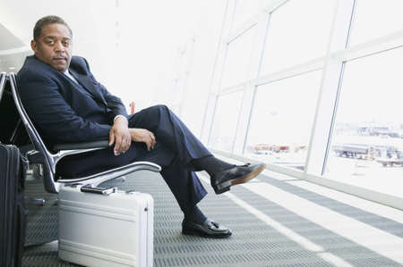 dapper: Portrait of a businessman sitting in a airport lounge with luggage looking into the camera LANG_EVOIMAGES