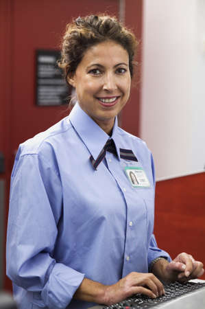 effrontery: Portrait of a female airport attendant standing at a counter LANG_EVOIMAGES