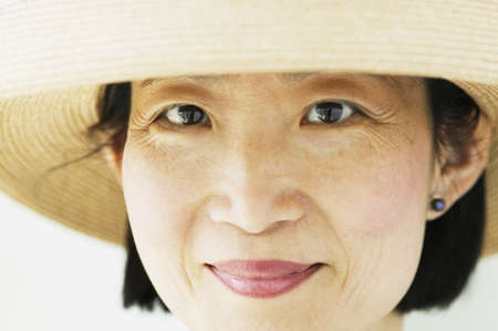 effrontery: Close-up of a mid adult woman wearing a sun hat