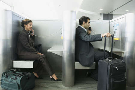 Side profile of a man and a woman using phone booths in an airport Stock Photo - 16043778
