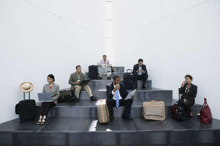 Group of business executives sitting on stairs with luggage Stock Photo - 16043780