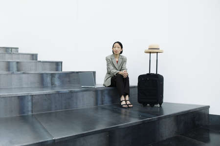 Businesswoman sitting on stairs with a baggage trolley Stock Photo - 16043781