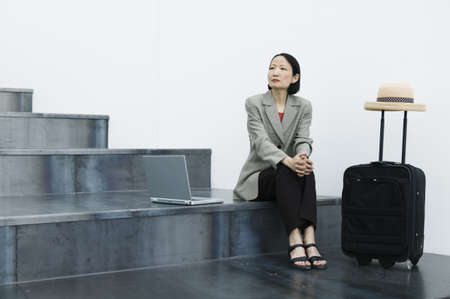 effrontery: Businesswoman sitting on stairs with a laptop and a baggage trolley LANG_EVOIMAGES