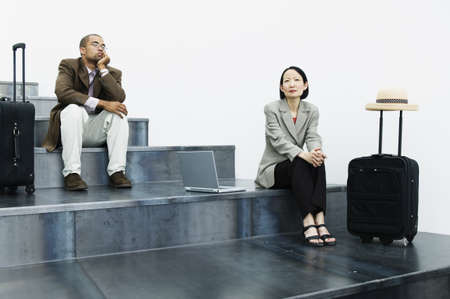 Two business executives sitting on stairs with baggage trolleys Stock Photo - 16043783