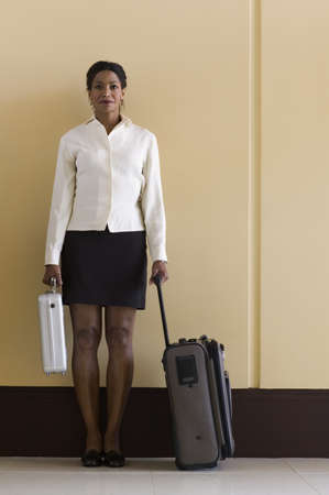Portrait of a young businesswoman standing with a baggage trolley Stock Photo - 16043790