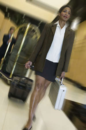 Low angle view of a young businesswoman walking in an airport with luggage Stock Photo - 16043792