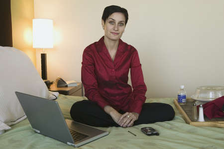 spanish woman: Portrait of a young businesswoman sitting on the bed in a hotel room