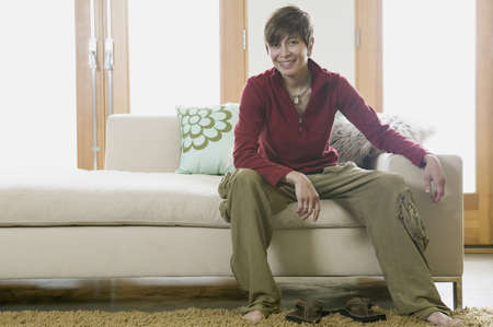 Portrait of a young woman sitting on a couch Stock Photo - 16043812