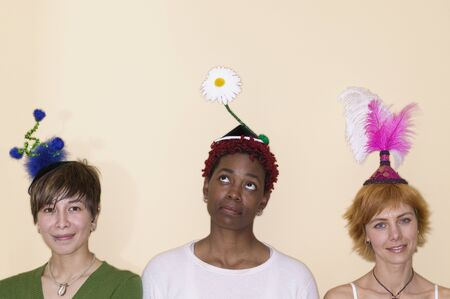 Portrait of three young women wearing abstract hats Stock Photo