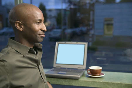 Young man sitting in front of a laptop Stock Photo - 16043843