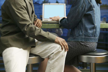 Young woman and a young man sitting operating a laptop Stock Photo - 16043846