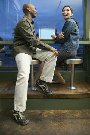 central european ethnicity: Pareja joven sentado juntos en taburetes delante de un ordenador port�til