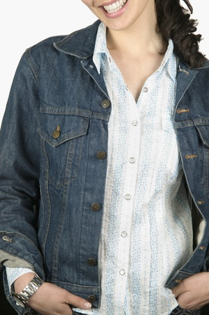 Young woman standing with her hands in her pockets smiling Stock Photo