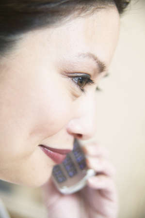 effrontery: Side profile of a young woman talking on a mobile phone LANG_EVOIMAGES