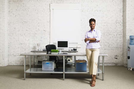 savvy: Businesswoman standing with arms folded leaning against a desk