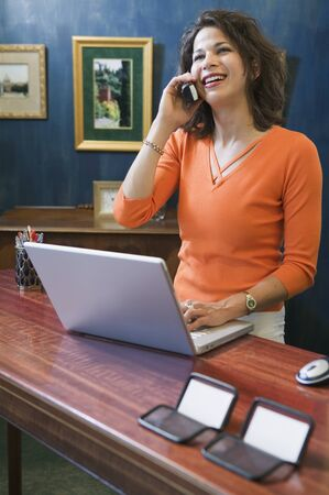 front desk: Young woman talking on a mobile phone standing in front of a laptop